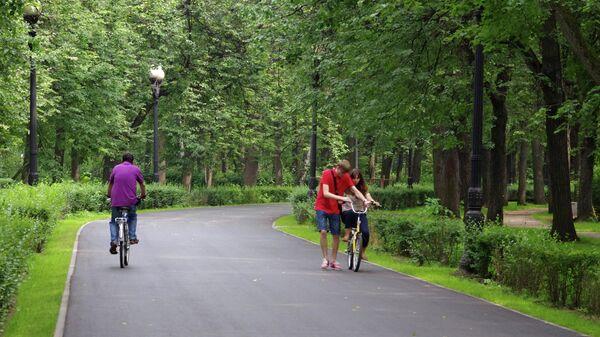 Юноша учит девушку ездить на велосипеде на одной из аллей Измайловского парка в Москве