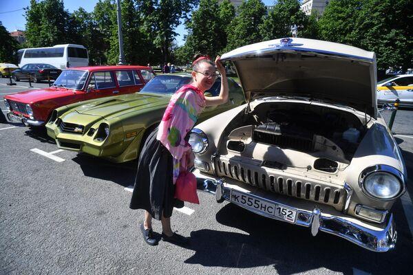 Девушка у автомобиля ГАЗ-21 Волга на выставке классических ретро-автомобилей в Москве