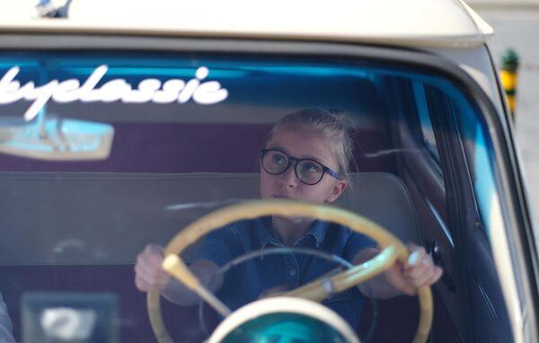 Девочка в ретро автомобиле, который принимает участие в ралли классических ретро-автомобилей в Москве