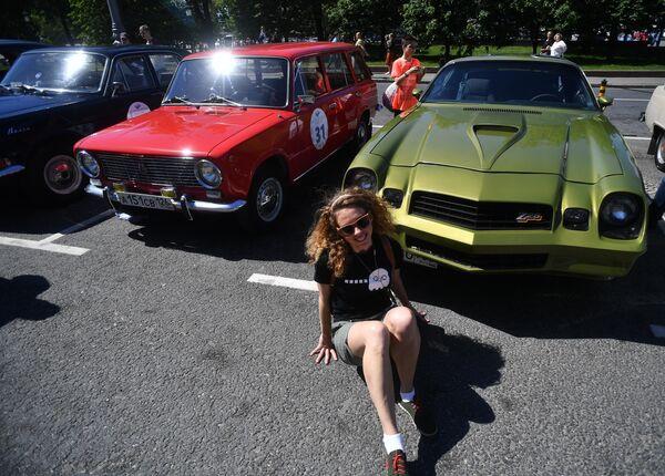 Девушка у автомобиля Chevrolet Camaro Z28 (1975-1979 гг. выпуска), который принимает участие в ралли классических ретро-автомобилей в Москве