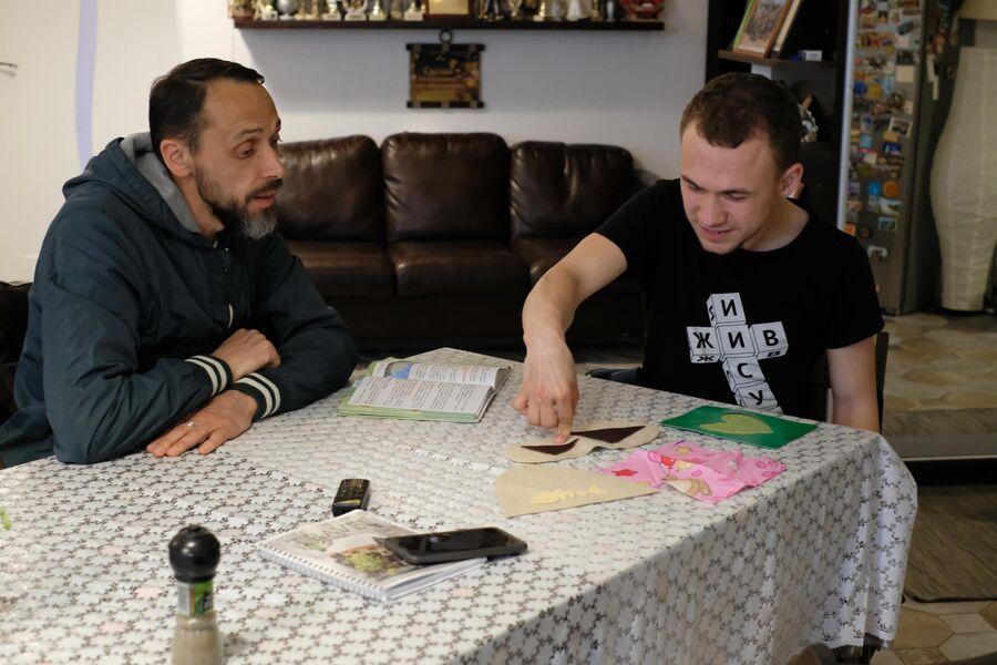 Витя показывает отцу Александру Горелову выкройки, которые он делал в колледже