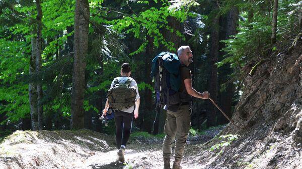 Туристы гуляют в лесу Северного отдела Кавказского государственного природного биосферного заповедника имени Х. Г. Шапошникова