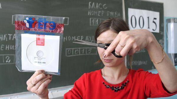 Учитель вскрывает пакет с диском, на котором содержатся задания для ЕГЭ по информатике и ИКТ