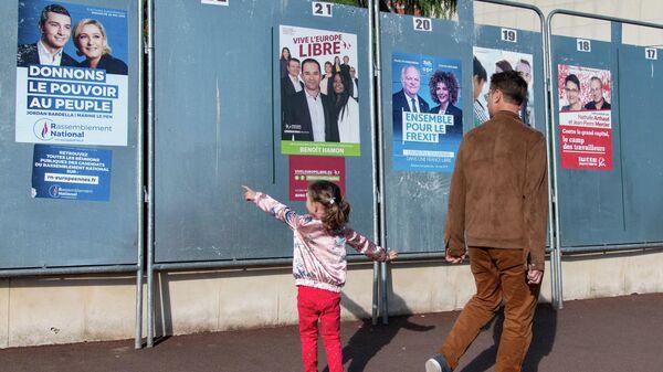 Избиратели у предвыборных плакатов кандидатов в заключительный день голосования на выборах в Европейский парламент у избирательного участка в Париже. 26 мая 2019