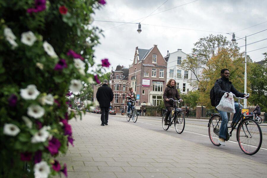 Горожане едут на велосипедах по одной из улиц в центре Амстердама