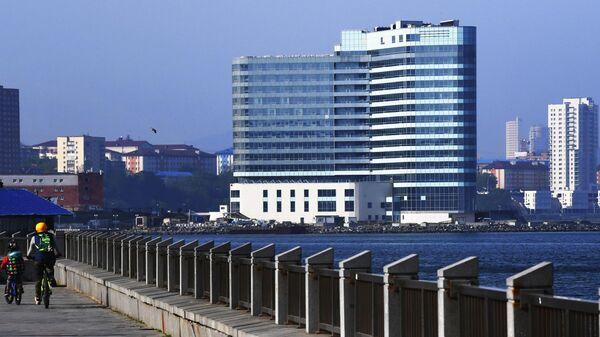 Местные жители катаются на велосипедах по набережной Спортивной гавани во Владивостоке