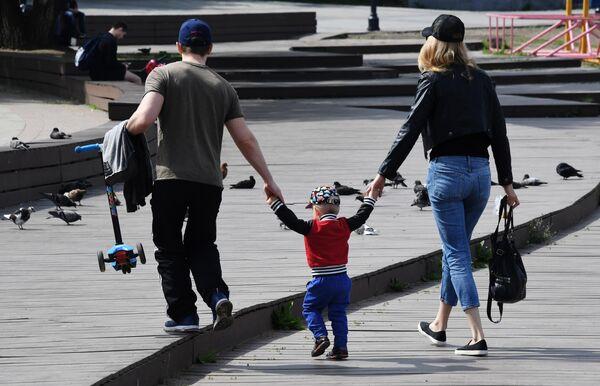 Семейная пара с ребенком гуляют по набережной Спортивной гавани во Владивостоке
