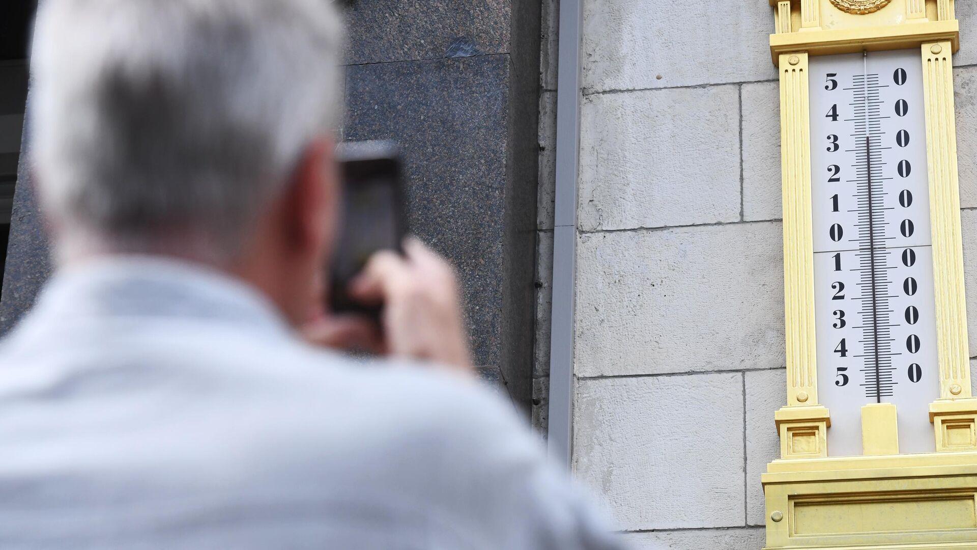 Мужчина фотографирует термометр на здании Государственной Думы РФ в Москве - РИА Новости, 1920, 18.05.2021