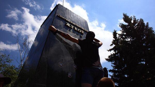 Представители националистических организаций сбивают надпись под бюстом маршала Георгия Жукова в Харькове возле Дворца спорта
