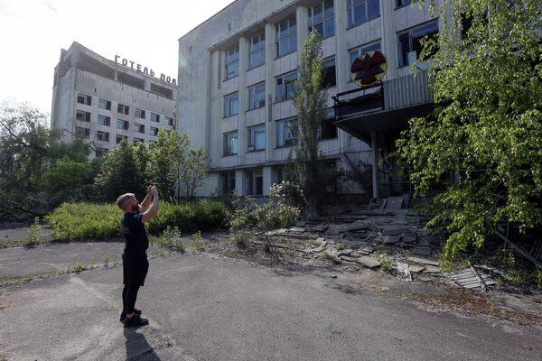 Турист фотографирует здание в заброшенном городе Припять, рядом с Чернобыльской АЭС, Украина