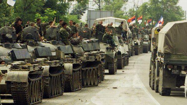 Российские военнослужащие проезжают мимо колонны югославских военных в Лазарево на пути к аэропорту Приштины