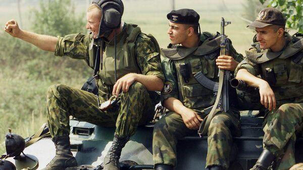 Российские солдаты приветствуют конвой, проходящий на территорию аэропорта Слатина
