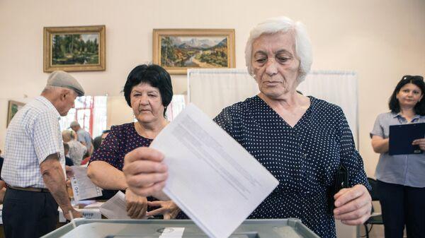 Женщина опускает бюллетень в урну для голосования на парламентских выборах в Южной Осетии. 9 июня 2019