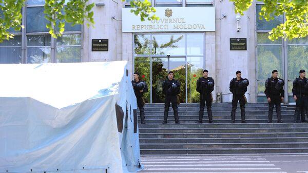 Сотрудники правоохранительных органов охраняют вход в здание правительства Молдавии во время митинга