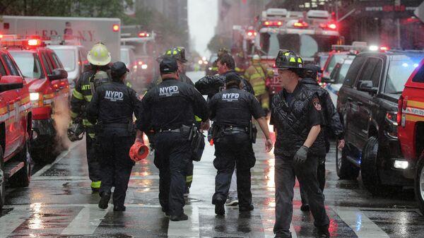 Сотрудники полиции и пожарные службы работают возле места крушения вертолета в Нью-Йорке