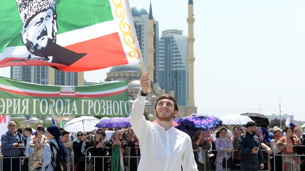Участник праздничного митинга, посвященного Дню России, на площади перед мечетью Сердце Чечни в Грозном
