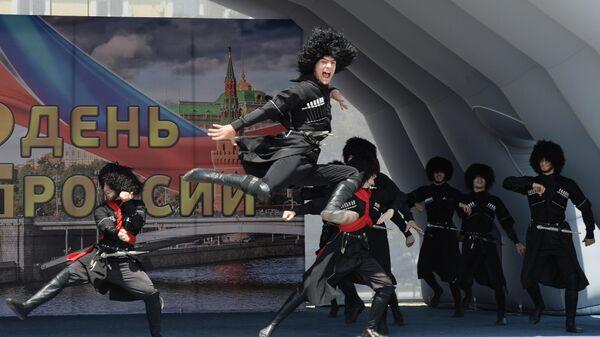 Участники ансамбля песни и танца Заманхо выступают на праздничном концерте, посвященном Дню России, на площади перед мечетью Сердце Чечни в Грозном