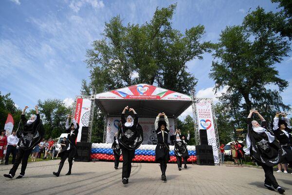 Молодые люди в национальных костюмах выступают на праздновании Дня России в парке им. М. Горького в Казани