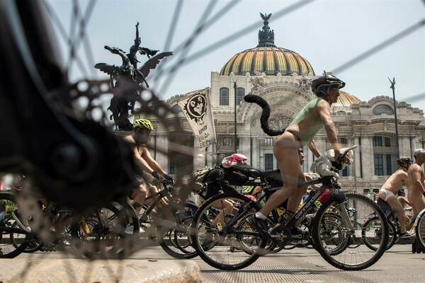 Велосипедисты едут по улицам Мехико во время празднования Всемирного голого велопробега