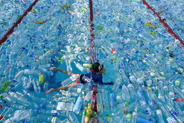 Ребенок плавает в бассейне наполненном пластиковыми бутылками во время информационной кампании по случаю Всемирного дня океанов в Бангкоке