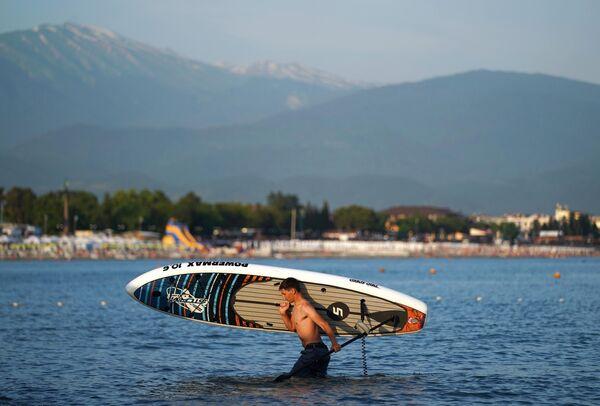 Мужчина с доской для саб-серфинга в районе Имеретинской низменности города Сочи