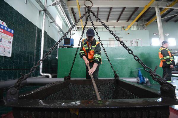 Сотрудник Мосводоcтока достает мусор из мусорозадерживающие корзины