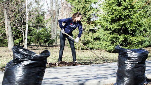 Девушка во время уборки прошлогодней листвы