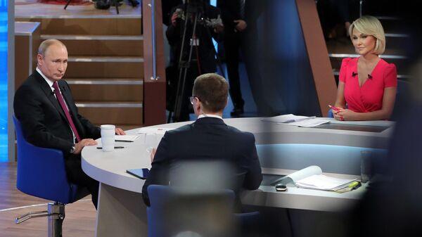 Президент РФ Владимир Путин, корреспондент ВГТРК Павел Зарубин и корреспондент Первого канала Елена Винник (слева направо) во время ежегодной специальной программы Прямая линия с Владимиром Путиным