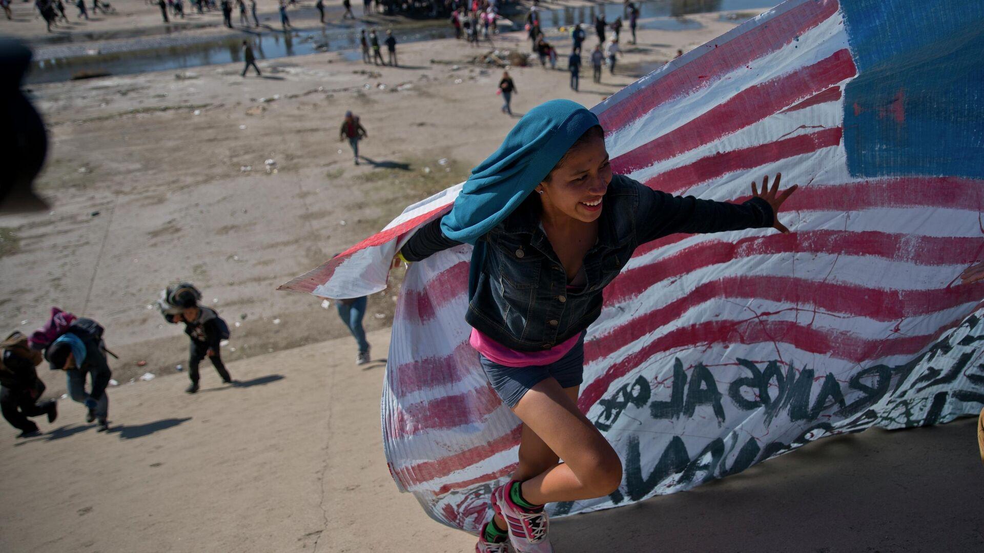 Мигрантка помогает нести американский флаг на границе Мексики и США - РИА Новости, 1920, 19.01.2021