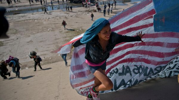 Мигрантка помогает нести американский флаг на границе Мексики и США
