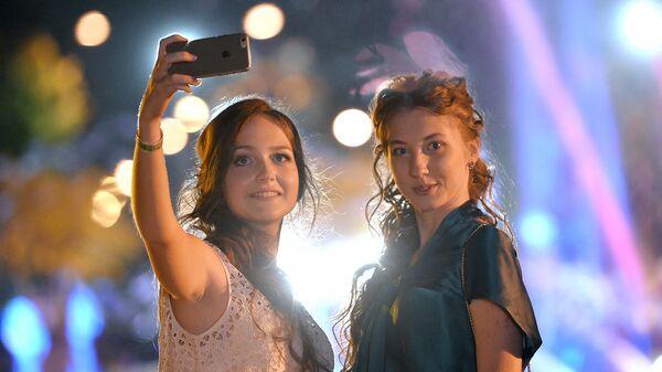 Выпускницы фотографируются на мобильный телефон