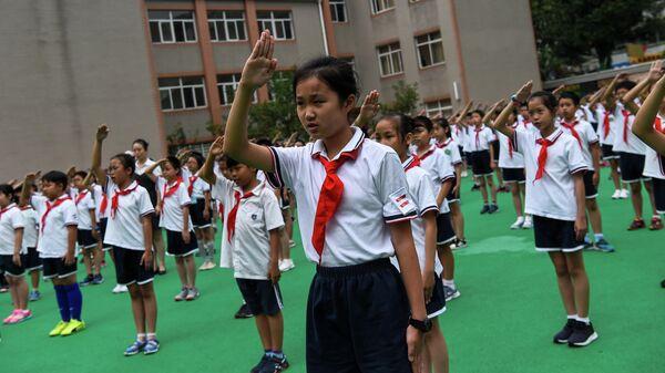 Ученики поют государственный гимн во время церемонии подъема флага в своей школе в Шанхае