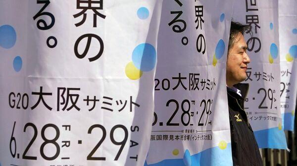 Мужчина с флагами с символикой саммита G20 в Осаке в Международном выставочном центре, Япония