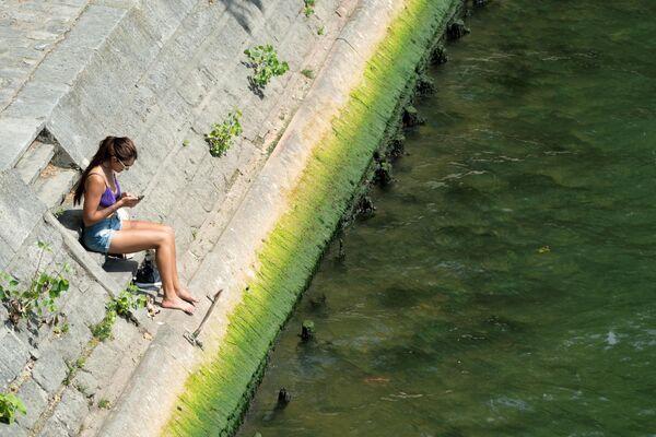 Женщина сидит на берегу реки Сены, Париж