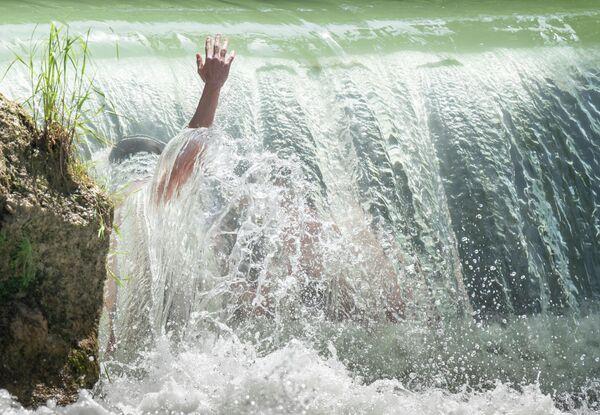 Дети купаются в Английском саду в Мюнхене, Германия