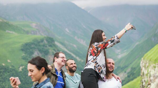 Туристы фотографируются на смотровой площадке у Военно-Грузинской дороги