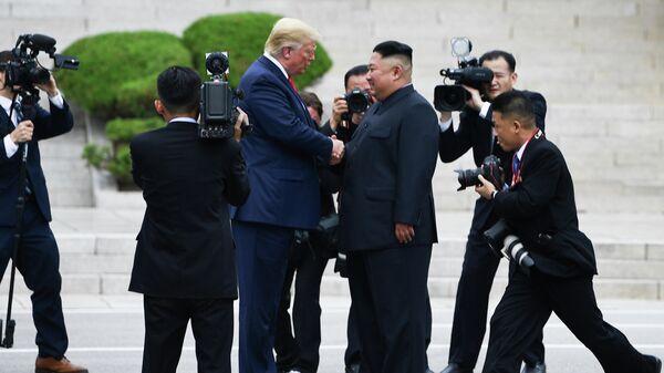 Лидер Северной Кореи Ким Чен Ын пожимает руку президенту США Дональду Трампу к северу от военной демаркационной линии, разделяющей Северную и Южную Корею в Демилитаризованной зоне. 30 июня 2019
