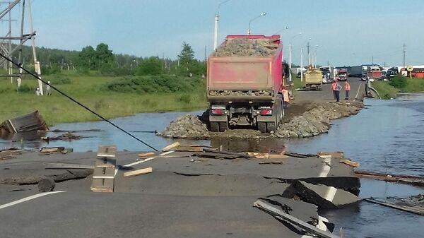 Самосвал насыпает щебень на разрушенном участке дороги в подтопленном городе Тулуне Иркутской области
