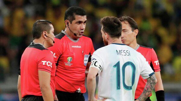 Нападающий сборной Аргентины Лионель Месси беседует с Родди Самбрано (второй слева), главным арбитром полуфинального матча Кубка Америки против Бразилии