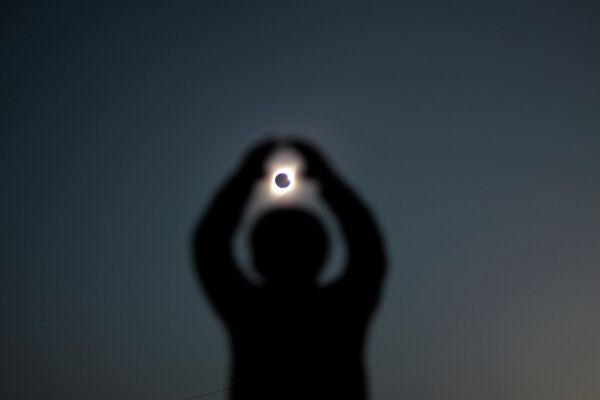 Человек во время солнечного затмения в Инкахуаси, Чили