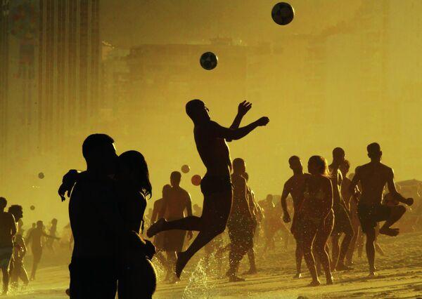 Люди играют с мячом на пляже Ипанема в Рио-де-Жанейро