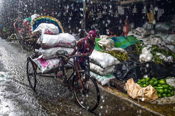 Рикша во время ливня в Дакке, Бангладеш