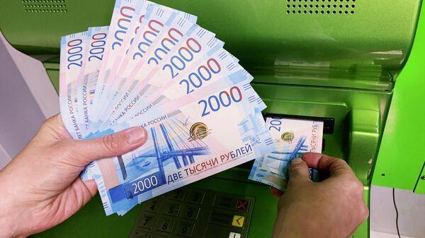Клиент Сбербанка вносит наличные деньги в банкомат