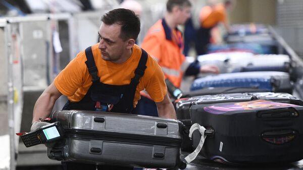 Сотрудник багажной службы во время работы в международном аэропорту Шереметьево в Москве