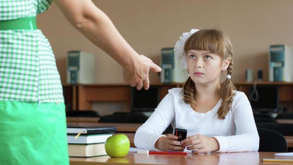 Учитель забирает мобильный телефон на уроке