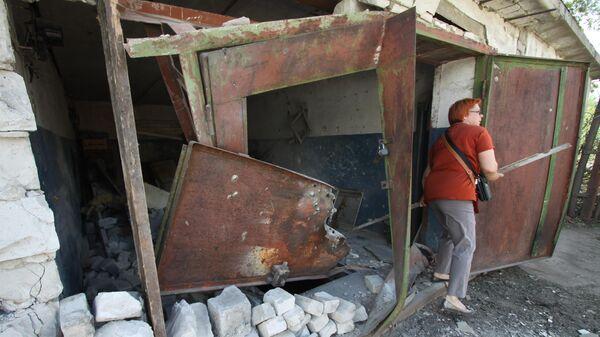 Жительница Горловки у гаража, разрушенного вследствие обстрела. 8 июля 2019