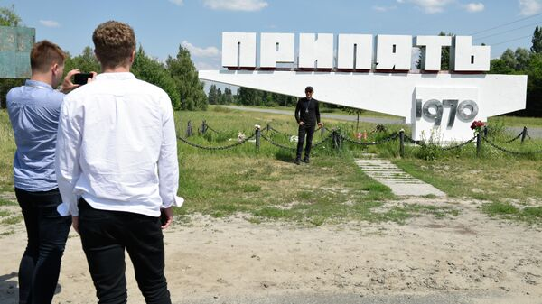 Туристы во время экскурсии в зону отчуждения Чернобыльской атомной электростанции в городе Припять