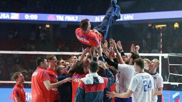 Мужская сборная России по волейболу подбрасывают главного тренера Туомаса Саммелвуо после победы