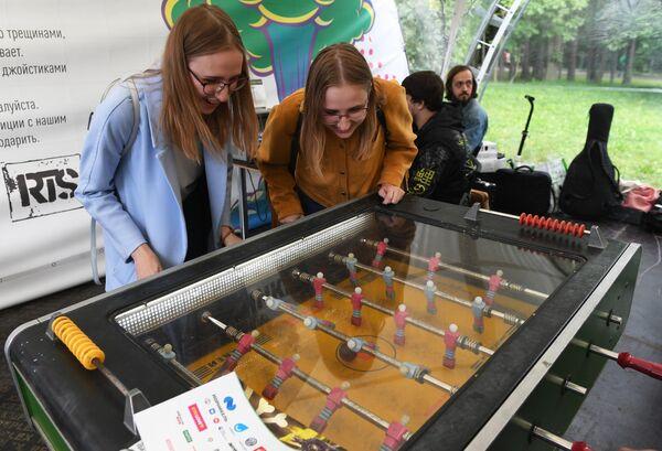 Девушки стоят у настольной игры в хоккей на фестивале науки и технологий Geek Picnic 2019 Жить вечно/Immortality