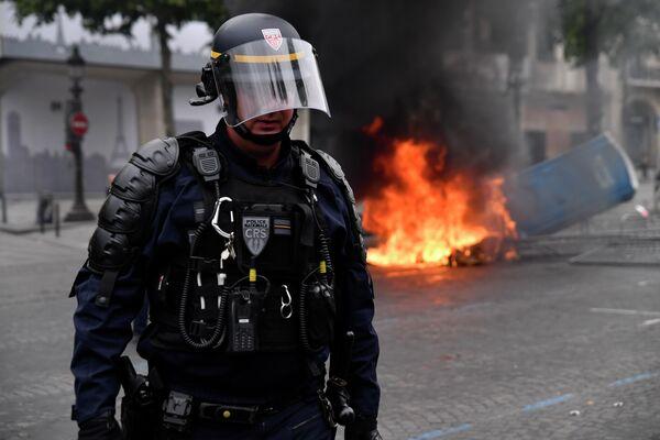 Сотрудник полиции во время беспорядков на Елисейских полях в Париже